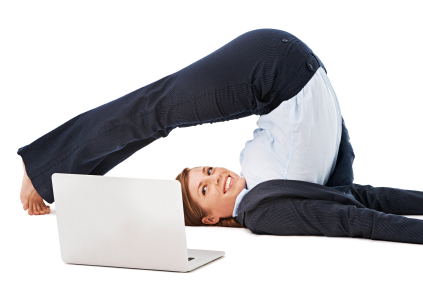 A young businesswoman stretching out her back while using a laptop