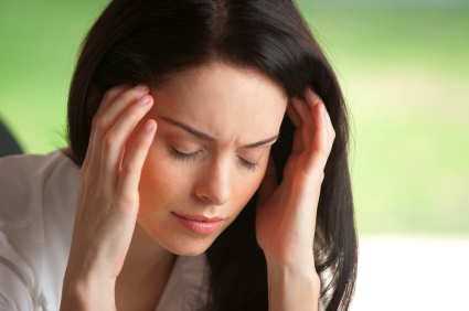 Attractive woman in pain holding her head